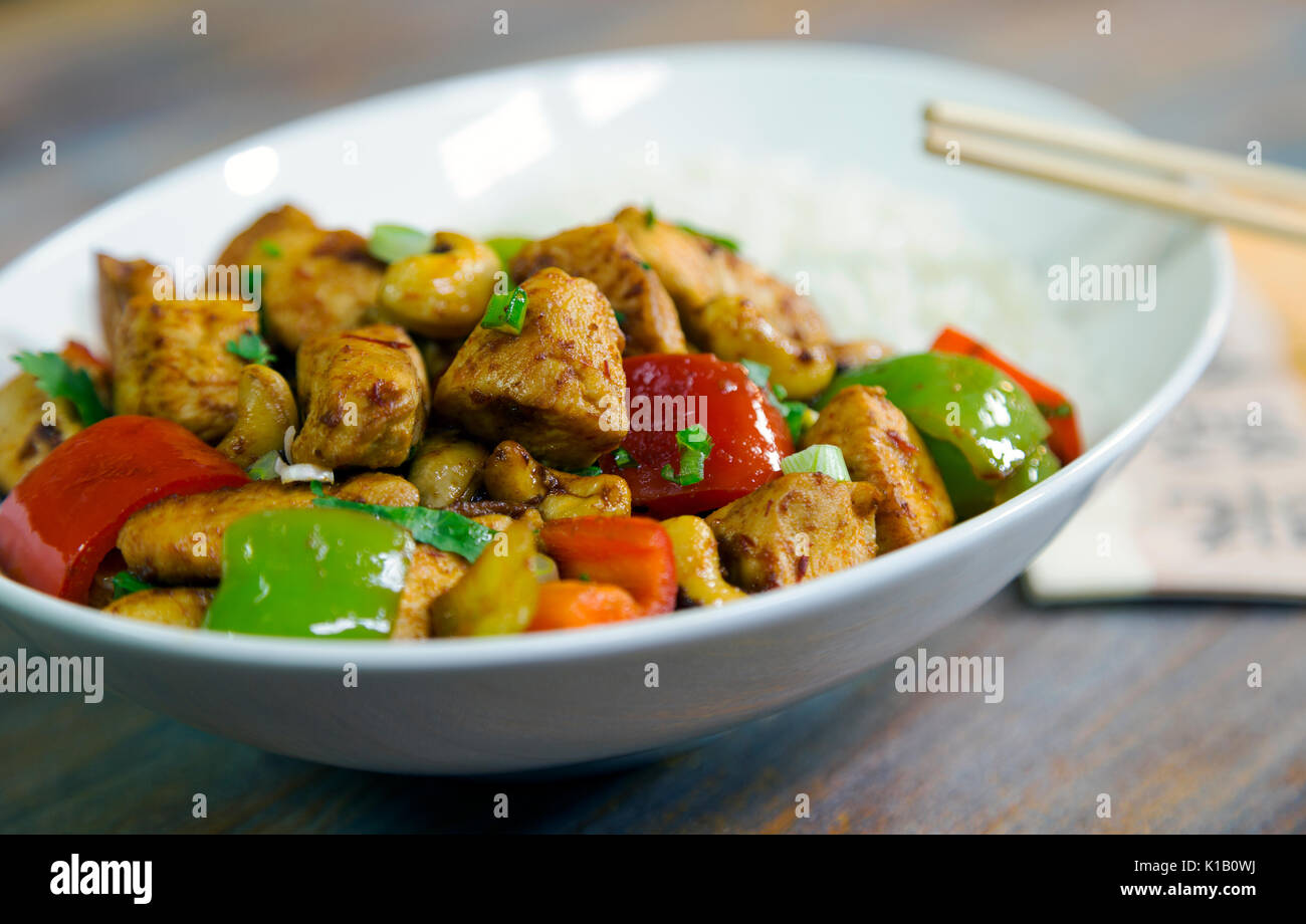 Freshly cooked Far Eastern chicken dish on a white plate with white rice untouched and ready to be eaten with nobody present - Stock Image
