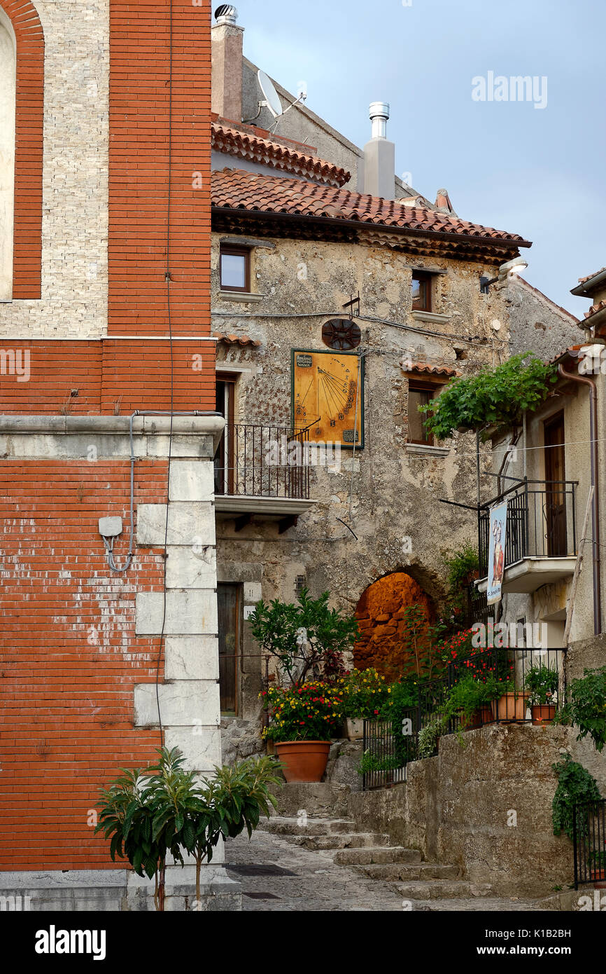 Suggestive corners of the Italian village. View of an ancient masonry building with illuminated passage and an ancient sundial for time measurement. M - Stock Image