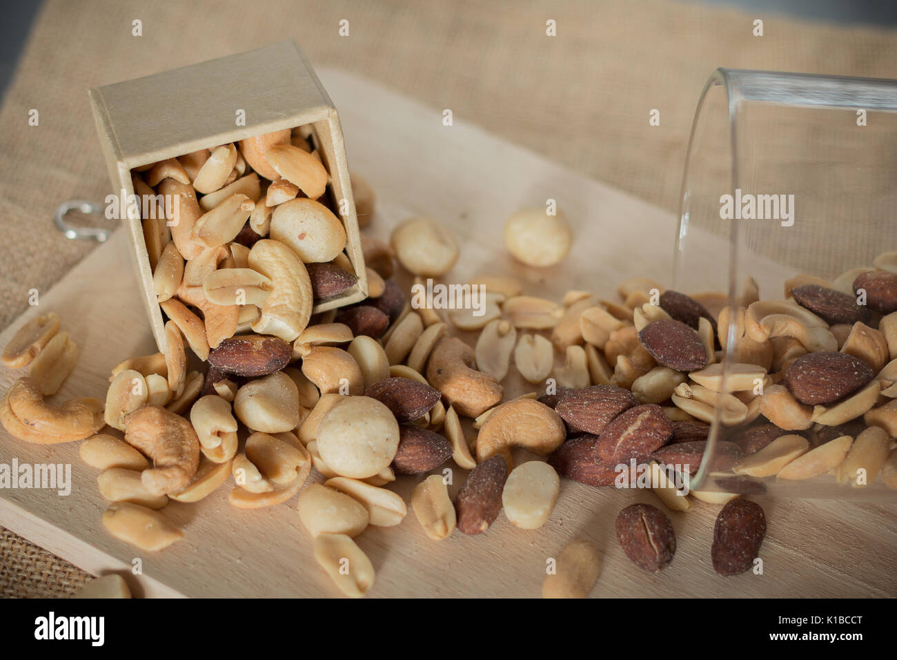 fresh roasted cocktail nuts (many type of nuts) on wooden plate - Stock Image