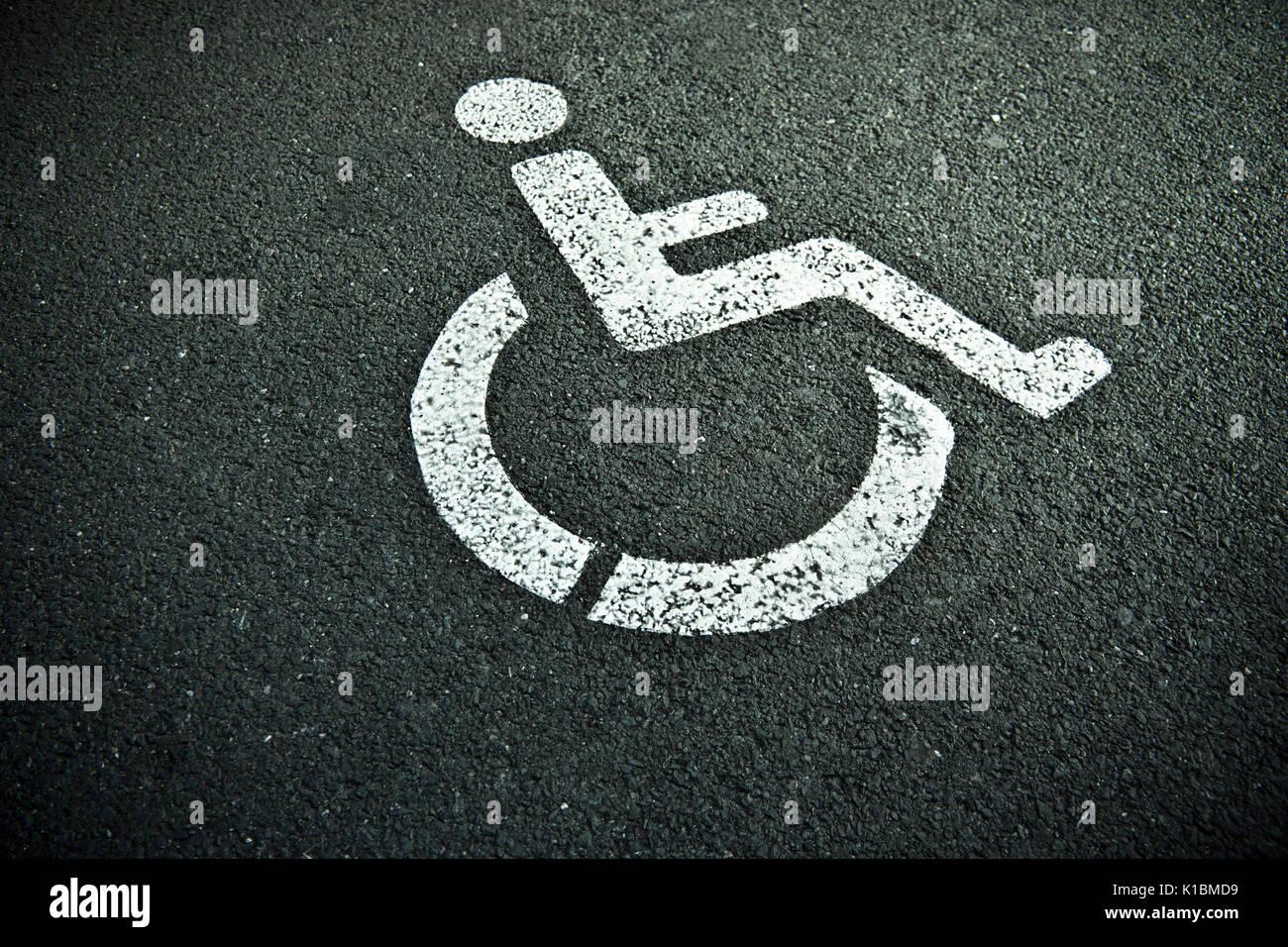 disabled sign on asphalt parking spot - Stock Image