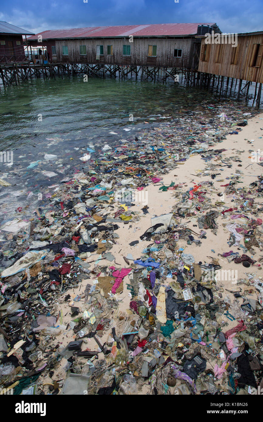 Plastic trash and other garbage covers a beach in front of budget dive resorts on Mabul Island, Borneo - Stock Image