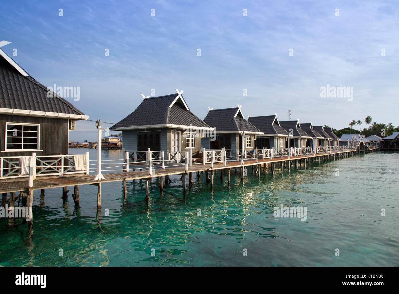Tourist bungalows over the ocean at Billabong Dive Resort, Mabul Island - Stock Image