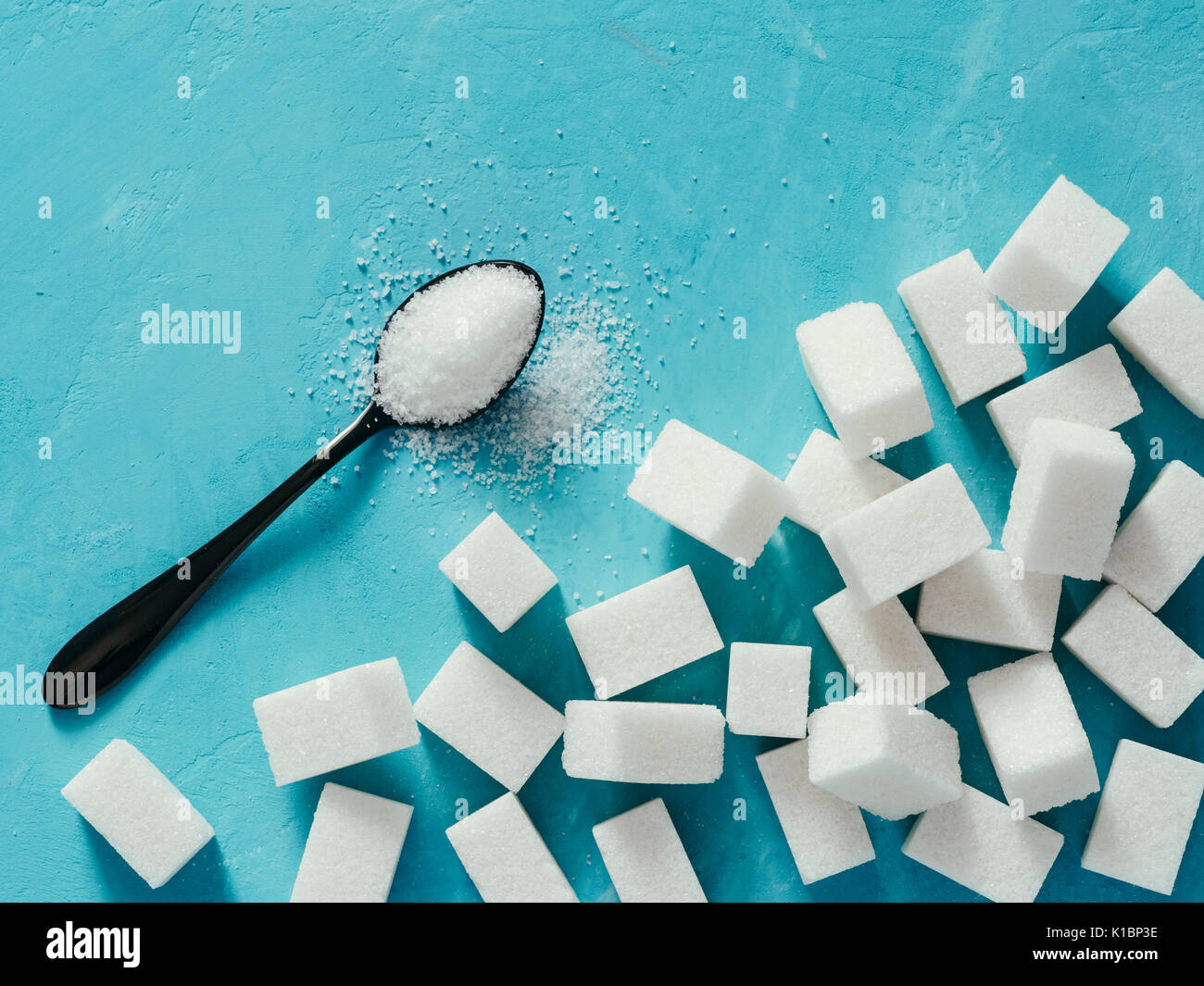 background of sugar cubes and sugar in spoon. White sugar on blue background. Sugar with copy space. Top view or flat lay - Stock Image