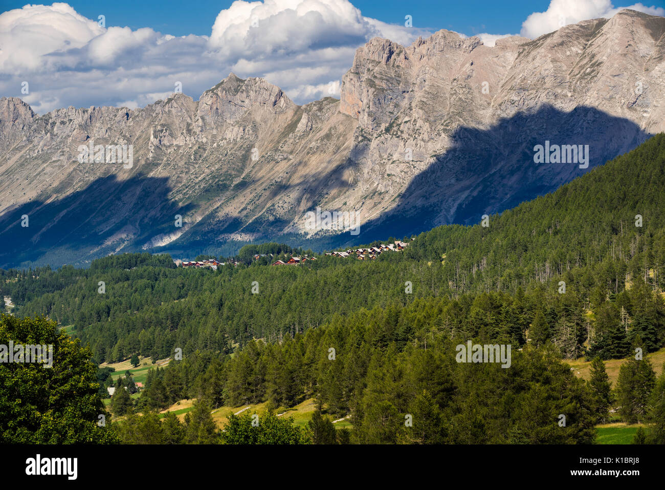 Summer in the Devoluy with chalets of La Joue du Loup (ski resort) and the peaks of the Faraut Mountain (Faraut Breccia and Pic de Cabournasse). Haute - Stock Image