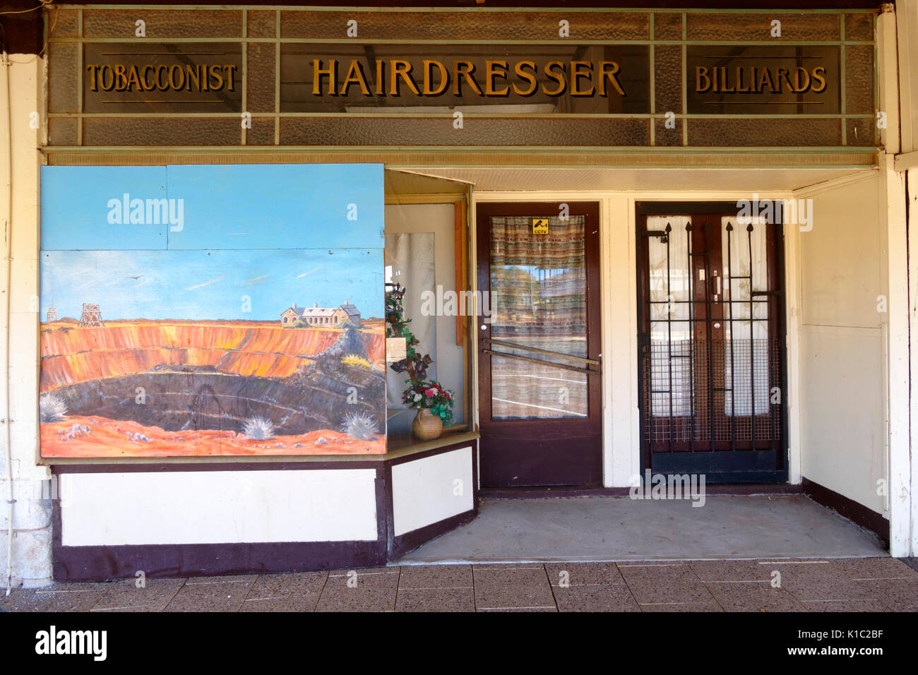 Hair dresser shop with mural of mining in window, Australian goldfields town, Cue, Murchison, Western Australia - Stock Image