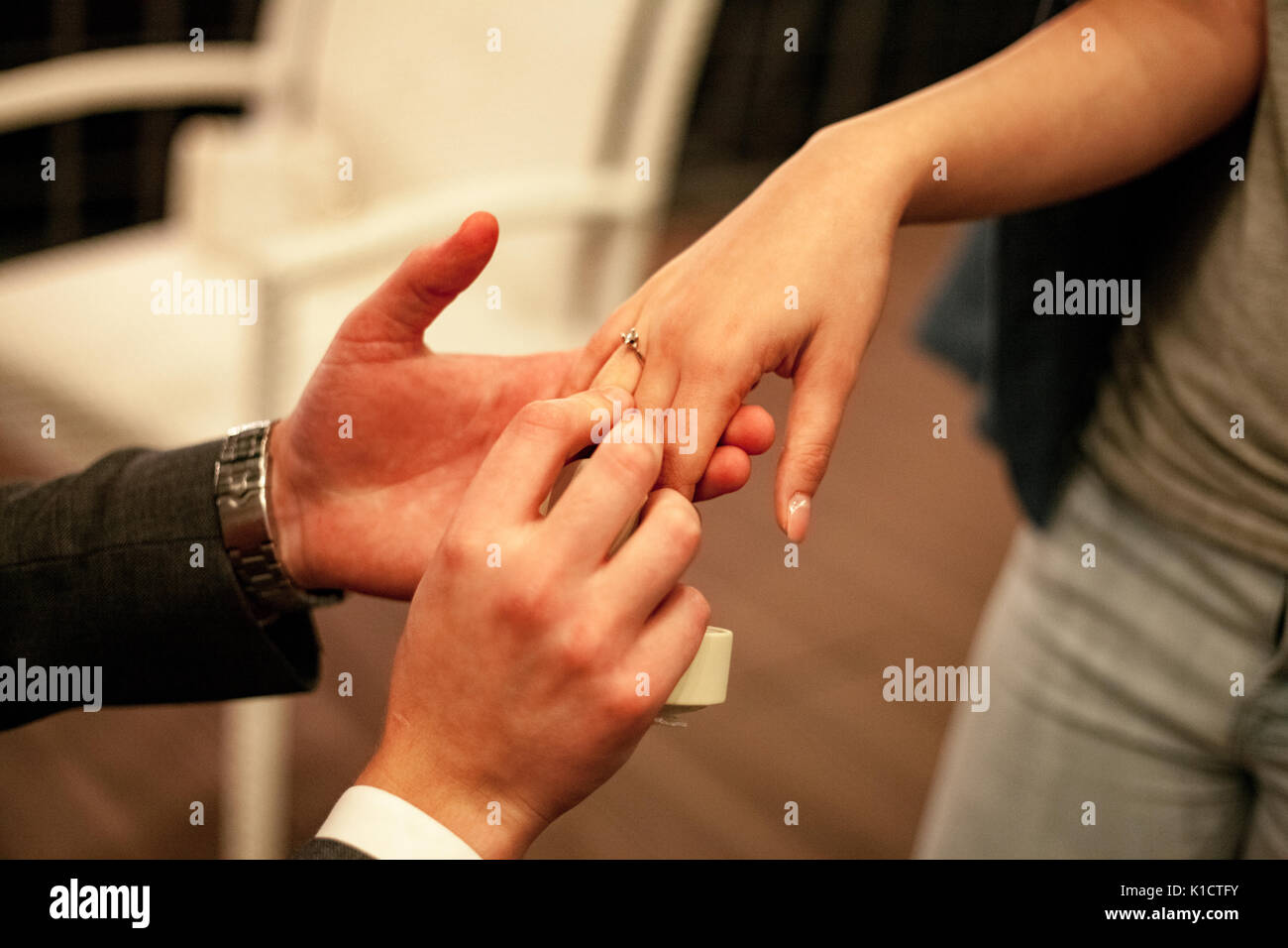 Man makes woman marriage proposal and puts on engagement ring with diamond on her finger. Close up. - Stock Image