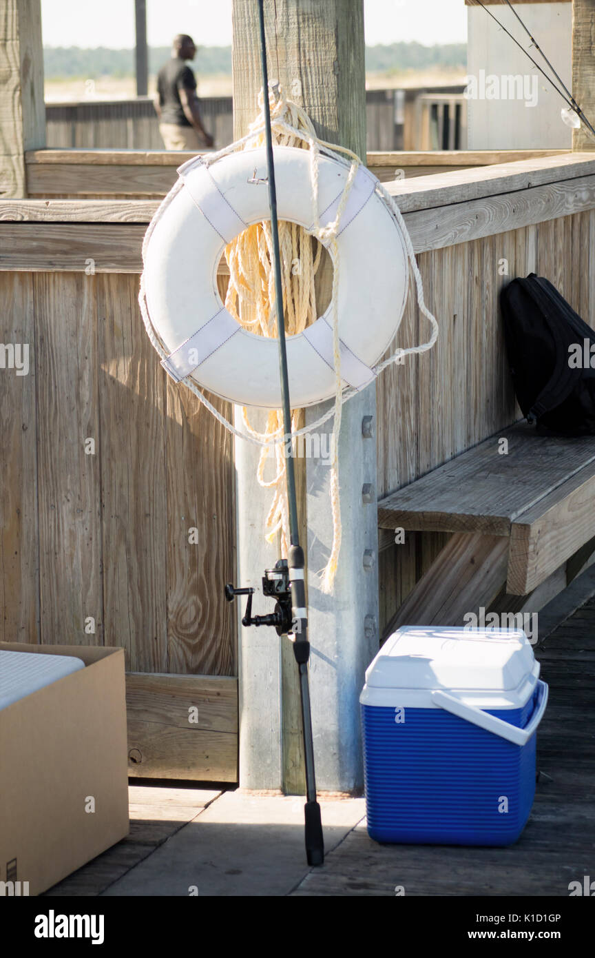 A Fishing rod sitting against a life saver and a blue lunch box on the Gulf Shores Pier. - Stock Image