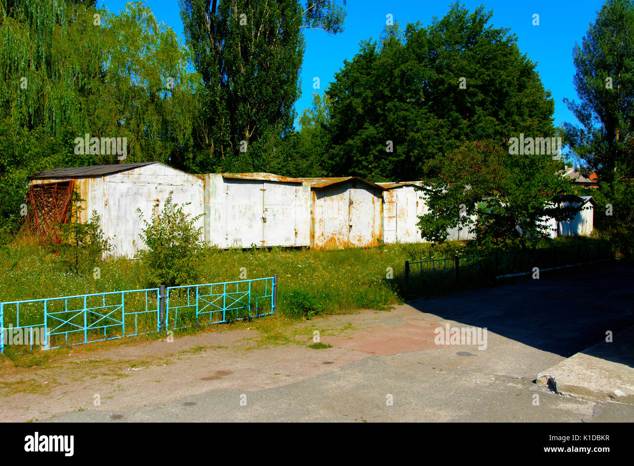 Old abandoned garages near houses. Dead radioactive zone. Consequences of the Chernobyl nuclear disaster, August 2017 - Stock Image