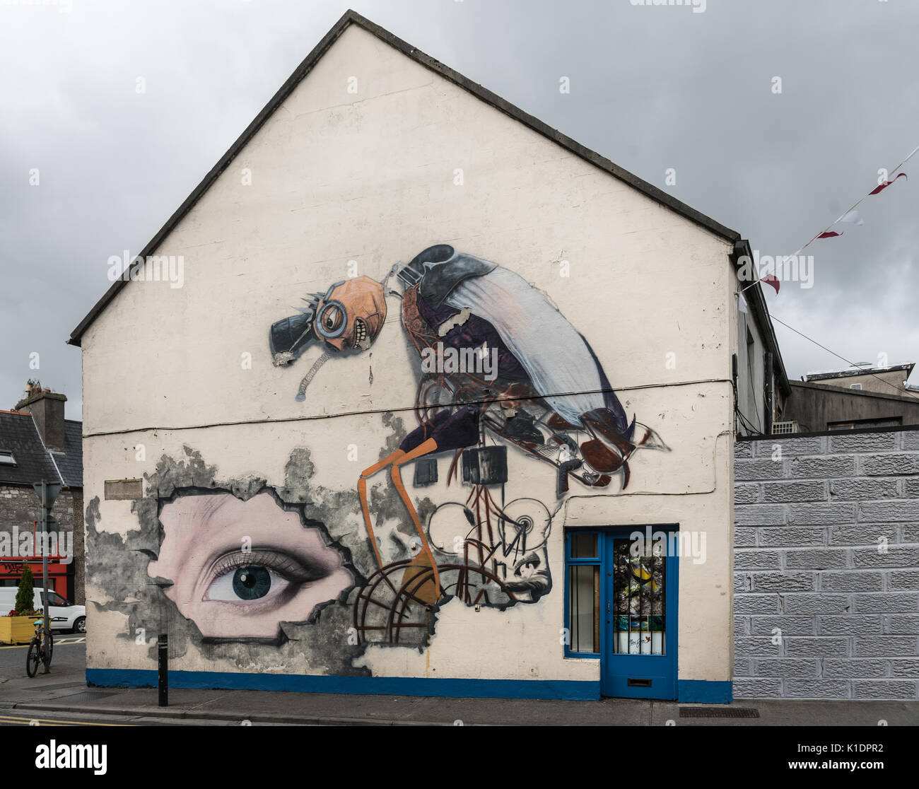 Galway, Ireland - August 3, 2017: Facade of house features a moder style cartoonish three dimensional image of large vulture with human face and glass - Stock Image