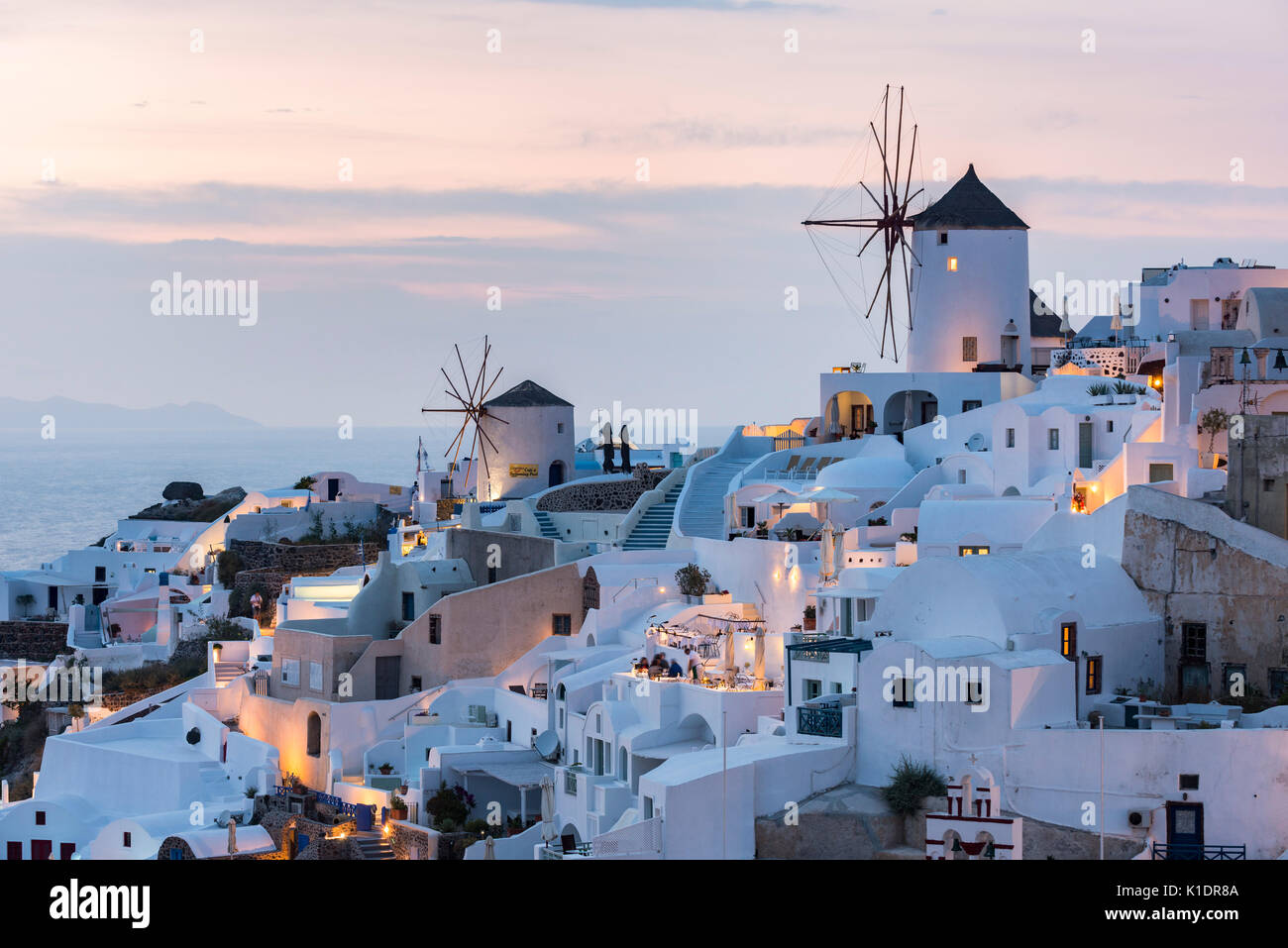 Townscape with windmills, dusk, Oia, Santorini, Cyclades, Greece - Stock Image