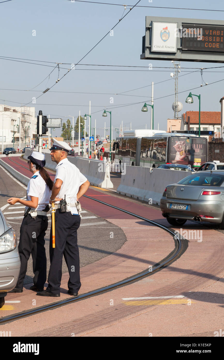Venice, Italy. 26th Aug, 2017. Anti-terror preparations for the 2017 Venice Film Festival due to start on the 30 August. Overnight the first of the concrete barriers have been installed in the Piazzale Roma to protect pedestrians and the tram lines from vehicular terror attacks. Two officers talking to a driver in a car at the entrance to Ponte della Liberta with the barriers behind. Credit: Mary Clarke/Alamy Live News - Stock Image
