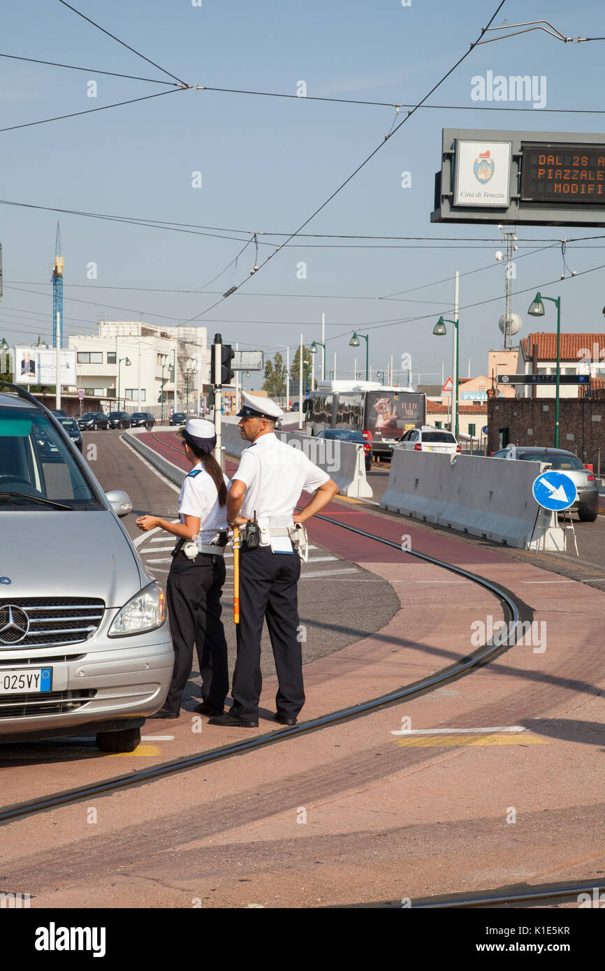 Venice, Italy. 26th Aug, 2017. Anti-terror preparations for the 2017 Venice Film Festival due to start on the 30 August. Overnight the first of the concrete barriers have been installed in the Piazzale Roma to protect pedestrians and the tram lines from vehicular terror attacks. Two police officers talking to the driver of a car on the tram lines entering Ponte della Liberta with the barriers behind. Credit: Mary Clarke/Alamy Live News - Stock Image