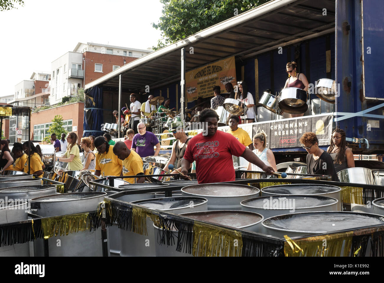 London, UK. 26th Aug, 2017. Steelpan Bands Panorama Notting Hill Carnival 2017. Steelpan bands prepare for judging at Horniman's Pleasance as London prepares to enjoy Notting Hill Carnival. Endurance, Metronome, Mangrove steelbands tune up. Brazilian drumming troupe Timbao entertains the waiting crowd and a Reggae's Got Talent looks for new reggae artistes and a poster cries out for Justice for Grenfell and First Aid is administered in a park near pissoir type public conveniences. Credit: Peter Hogan/Alamy Live News - Stock Image