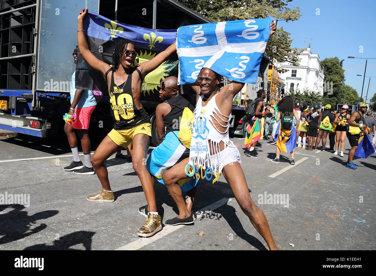 Thousands of revellers and spectators enjoy this year's Notting Hill Carnival with a colourful procession. Under the shadow of Grenfell Tower a one minute silence was observed. - Stock Image