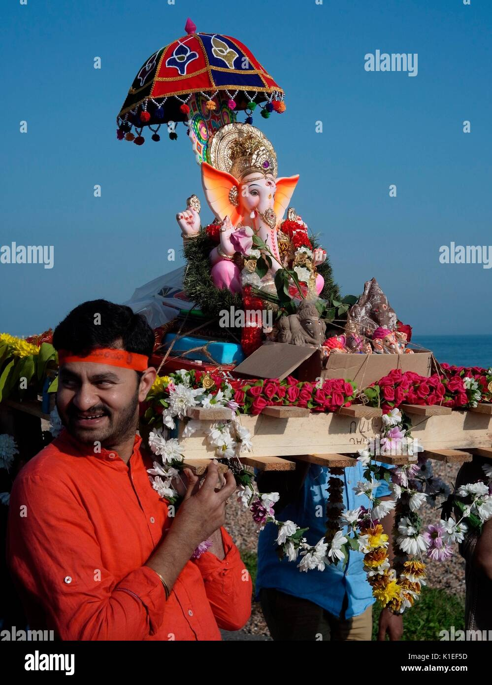 Worthing, UK. 27th Aug, 2017. Celebrating Ganesh Festival in the U.K. - Members of the local Hindu community carry a model of Lord Ganesh along the beach front to the English Channel. Also known as Ganesh Chaturthi, the important festival celebrates the elephant-headed son of Lord shiva and Goddess Parvati, a symbol of wisdon, prosperity and good fortune. The model is made of plaster of paris and dissolves in sea-water. Credit: Photo: Jonathan Eastland/Ajax/Alamy Live News - Stock Image