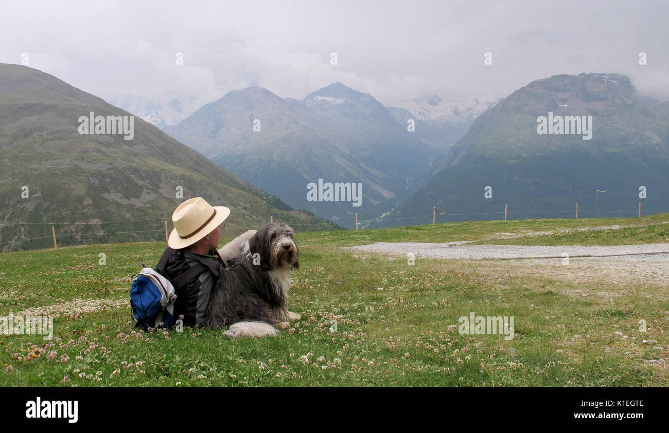 Graubunden, Switzerland. 20th July, 2017. A hiker and his dog resting in Muottas Muragl - a good 2500 meters high - in the canton of Graubunden, Switzerland, 20 July 2017. Picking up one's own dog's waste is par for the course even in fields, meadows and hiking trails in Switzerland. Photo: Christiane Oelrich/dpa/Alamy Live News - Stock Image