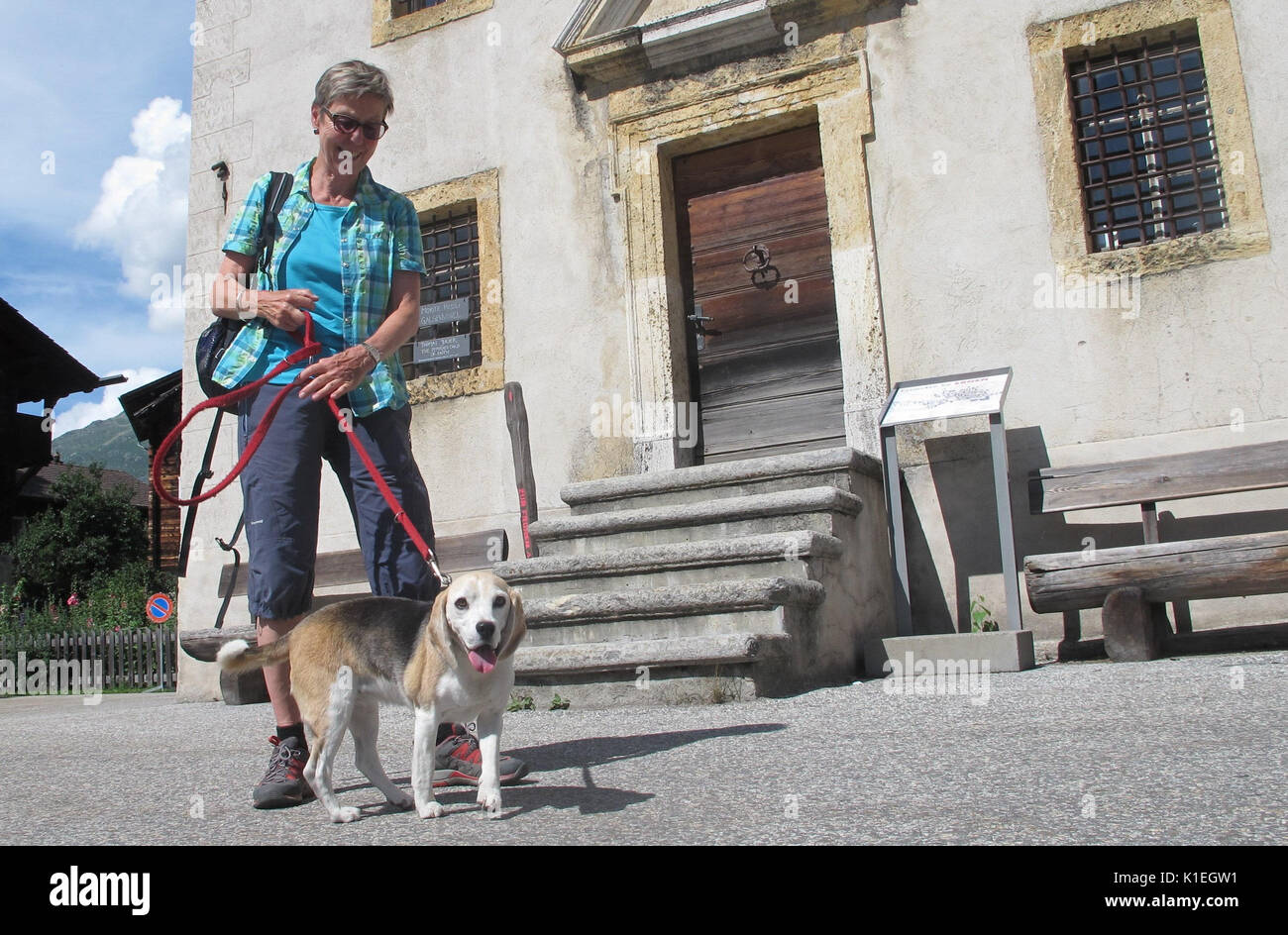 Wallis, Switzerland. 17th July, 2017. Ursula von Matt with her dog Selena in Ernen in the canton of Wallis, Switzerland, 17 July 2017. Picking up one's own dog's waste is par for the course even in fields, meadows and hiking trails in Switzerland. Photo: Christiane Oelrich/dpa/Alamy Live News - Stock Image