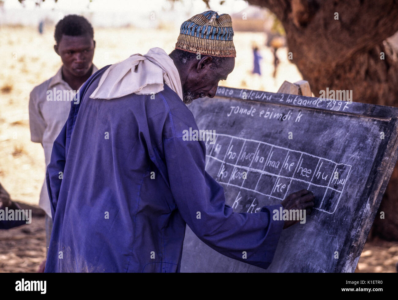 Niger, Doutouel Village, West Africa.  Man Practicing Writing in Adult Literacy Class. - Stock Image