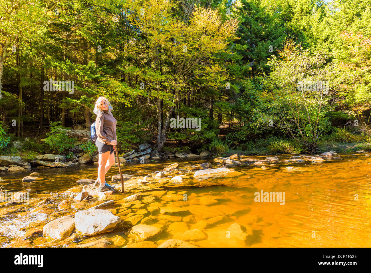 Young woman with stick crossing Red Creek river in Dolly Sods, West Virginia smiling - Stock Image