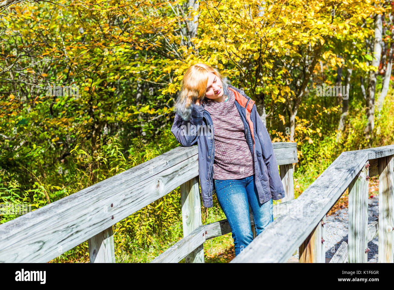 Young woman leaning on small wooden bridge in autumn smiling thinking Stock Photo