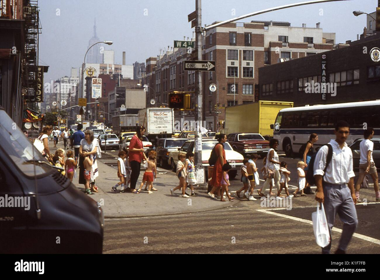This 1988 photograph depicted numbers of children as they were being helped by adults safely across a New York City street. Reflecting concern for children's safety, the New York City, Department of Transportation (NYCDOT) initiated a 'Walk to School Program' in 2005. New York City (NYC) is a high-pedestrian activity locale. Nine out of 10 Bronx children, for example, walk to school. Besides safety concerns, the 'Walk to School Program' benefits include more physical activity for children and adults in neighborhoods, less traffic and harmful emissions, reduced crime because more people are out - Stock Image