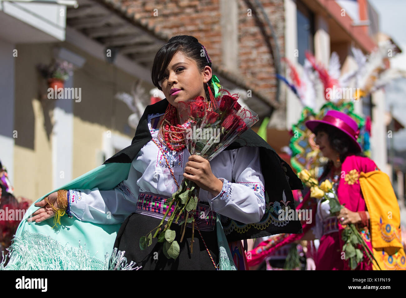June 17, 2017 Pujili, Ecuador: woman wearing a colorful costume marching at the annual Corpus Christi parade holding flowers - Stock Image