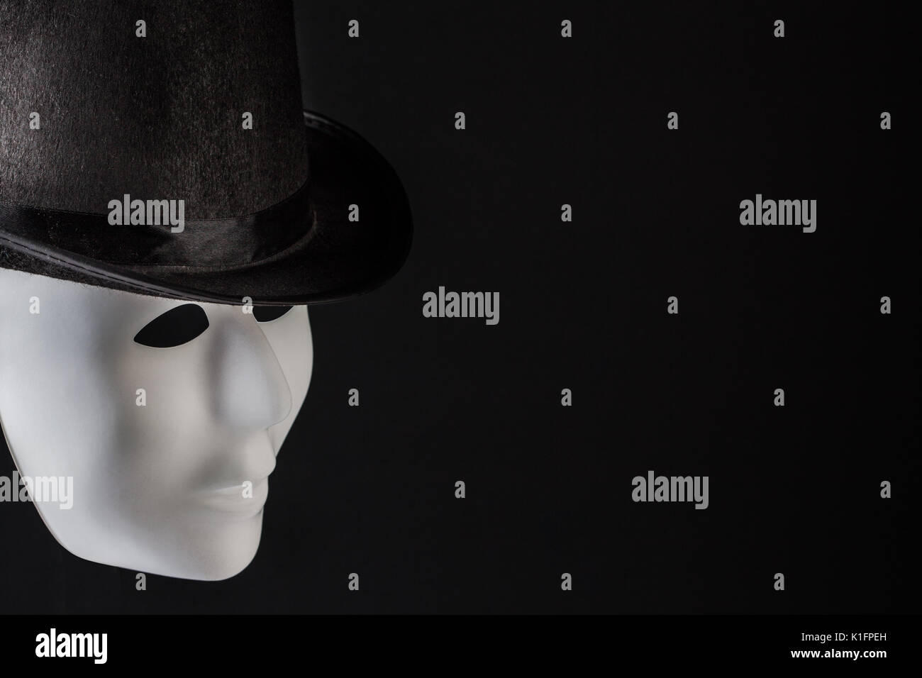 White mask profile wearing black top hat isolated on black background with copy space - Stock Image