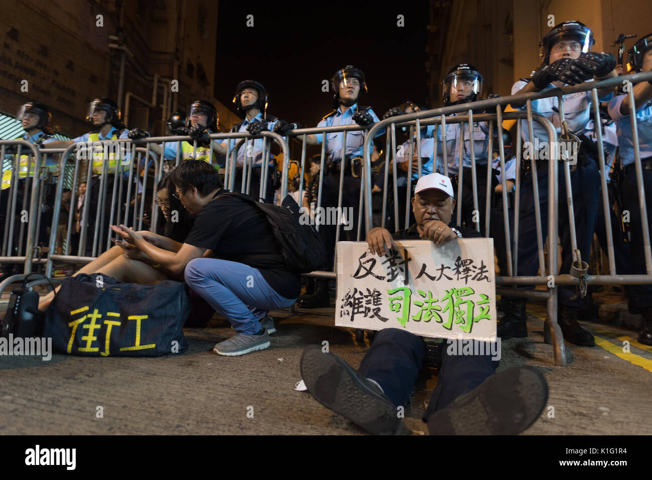 A man sits down before the police with a board demanding the respect of the 'One country two systems' principle in Hong Kong. - Stock Image