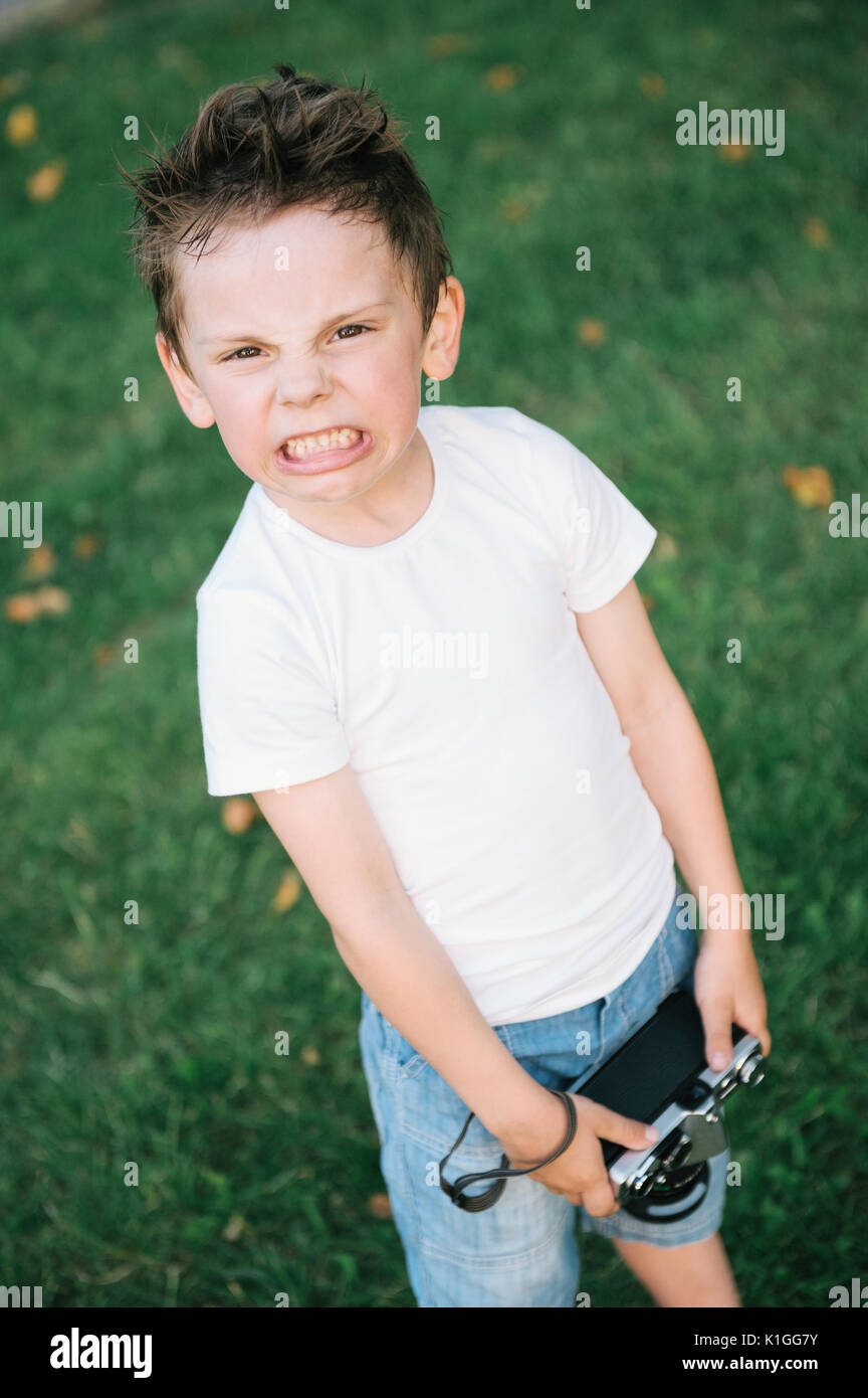 Angry little boy with a grimace on his face holding film camera on green grass backdrop - Stock Image