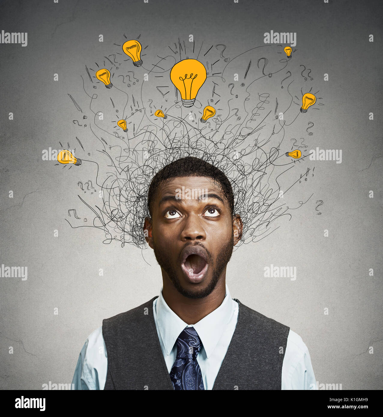 Young man with many idea light bulbs above head looking up isolated on gray wall background. - Stock Image