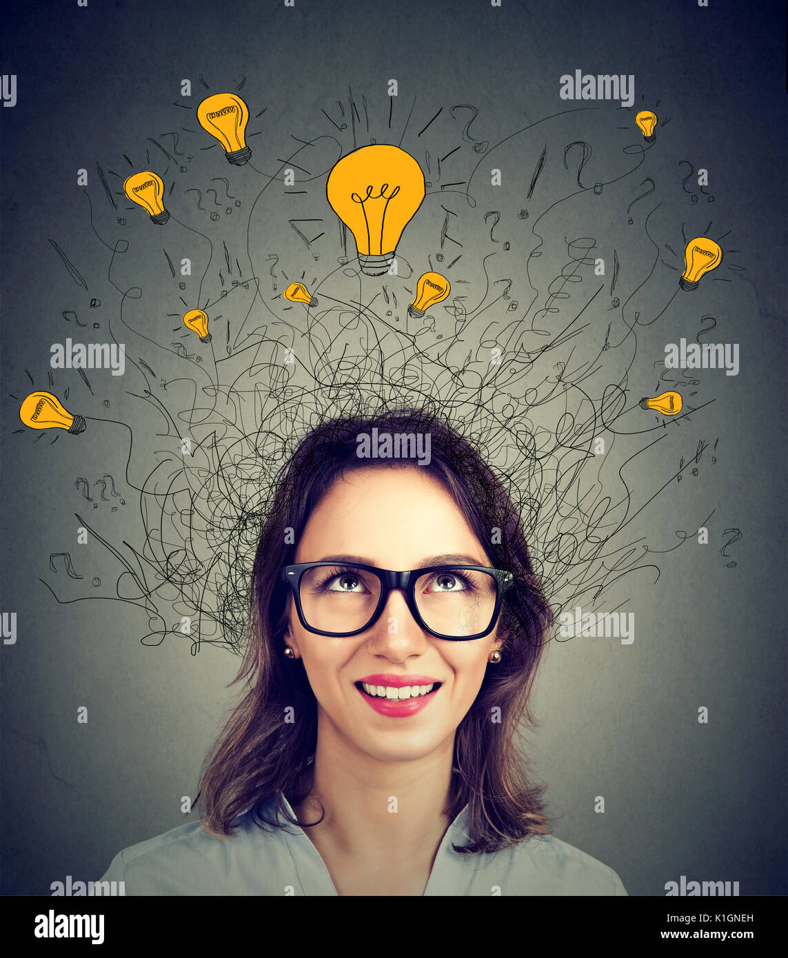 Young woman in glasses with many ideas light bulbs above head looking up isolated on gray wall background. Eureka creativity concept - Stock Image