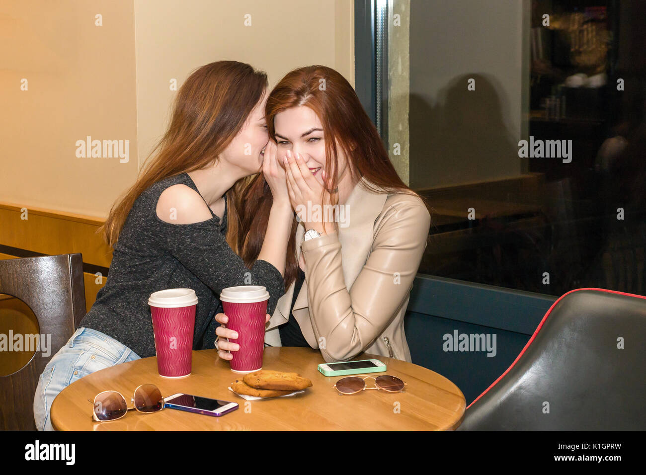 Two beautiful women drinking coffee mug, gossiping and chatting in a cafe bar. Two girls sitting in a cafeteria, Stock Photo