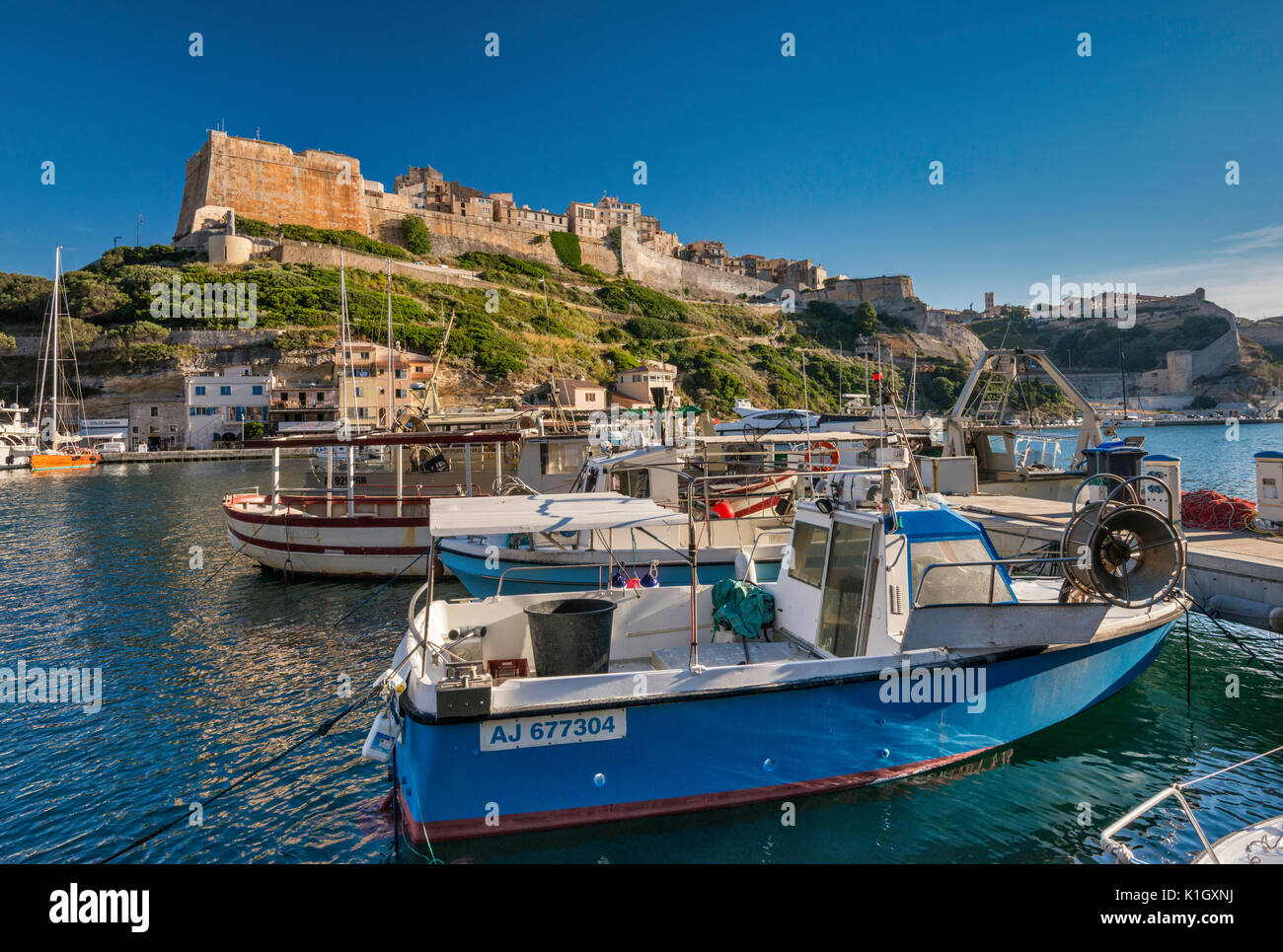 Citadelle, boats at marina at port, at sunset in Bonifacio, Corse-du-Sud, Corsica, France - Stock Image