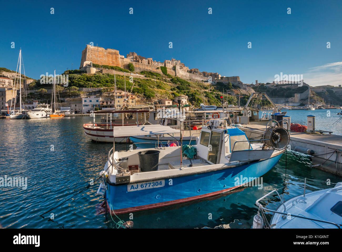 Citadelle, boats at marina at port, at sunset in Bonifacio, Corse-du-Sud, Corsica, France - Stock Image