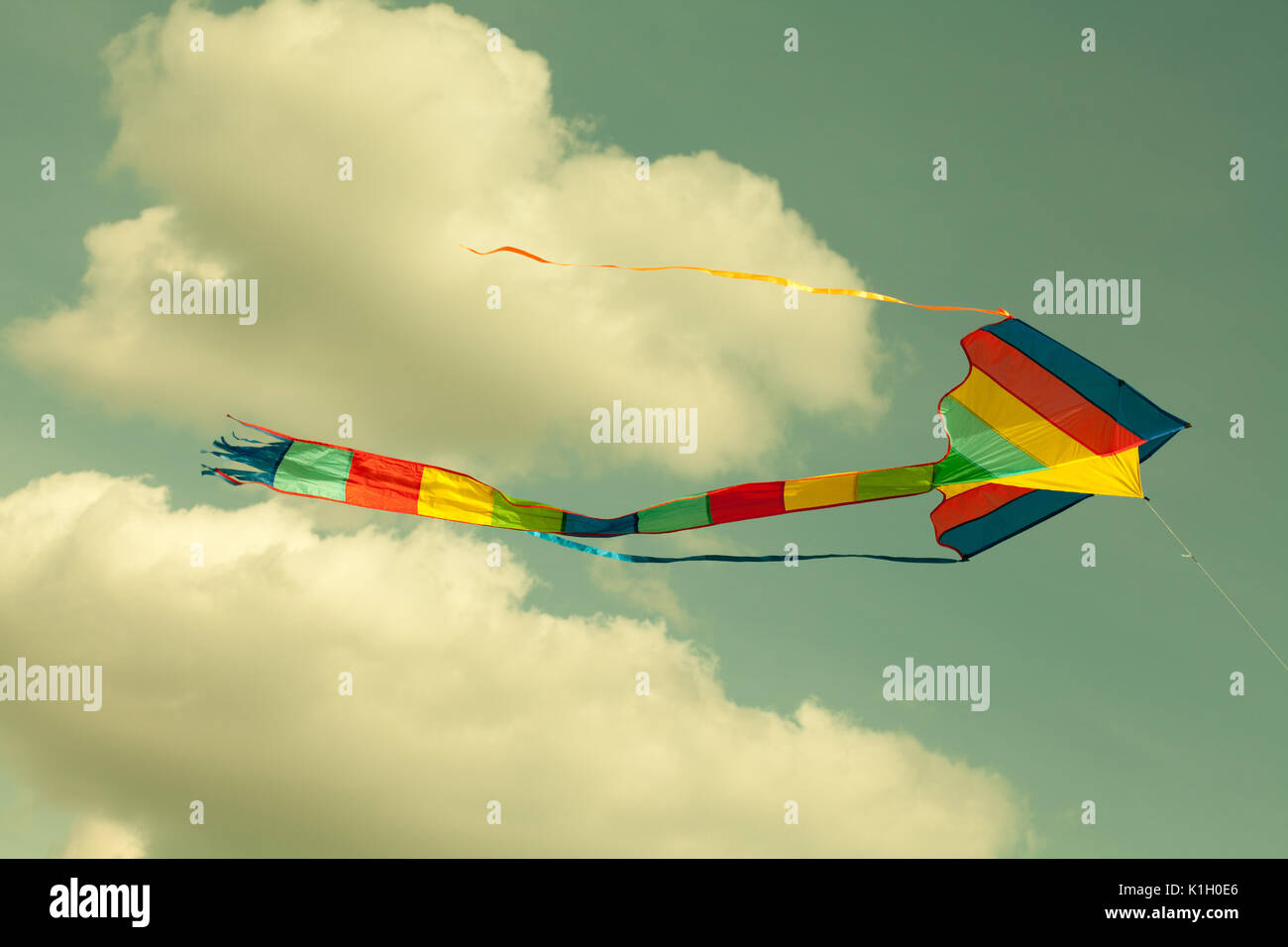 Multicolor kite flying in the cloudy sky. Retro style. (Toned photo.) - Stock Image