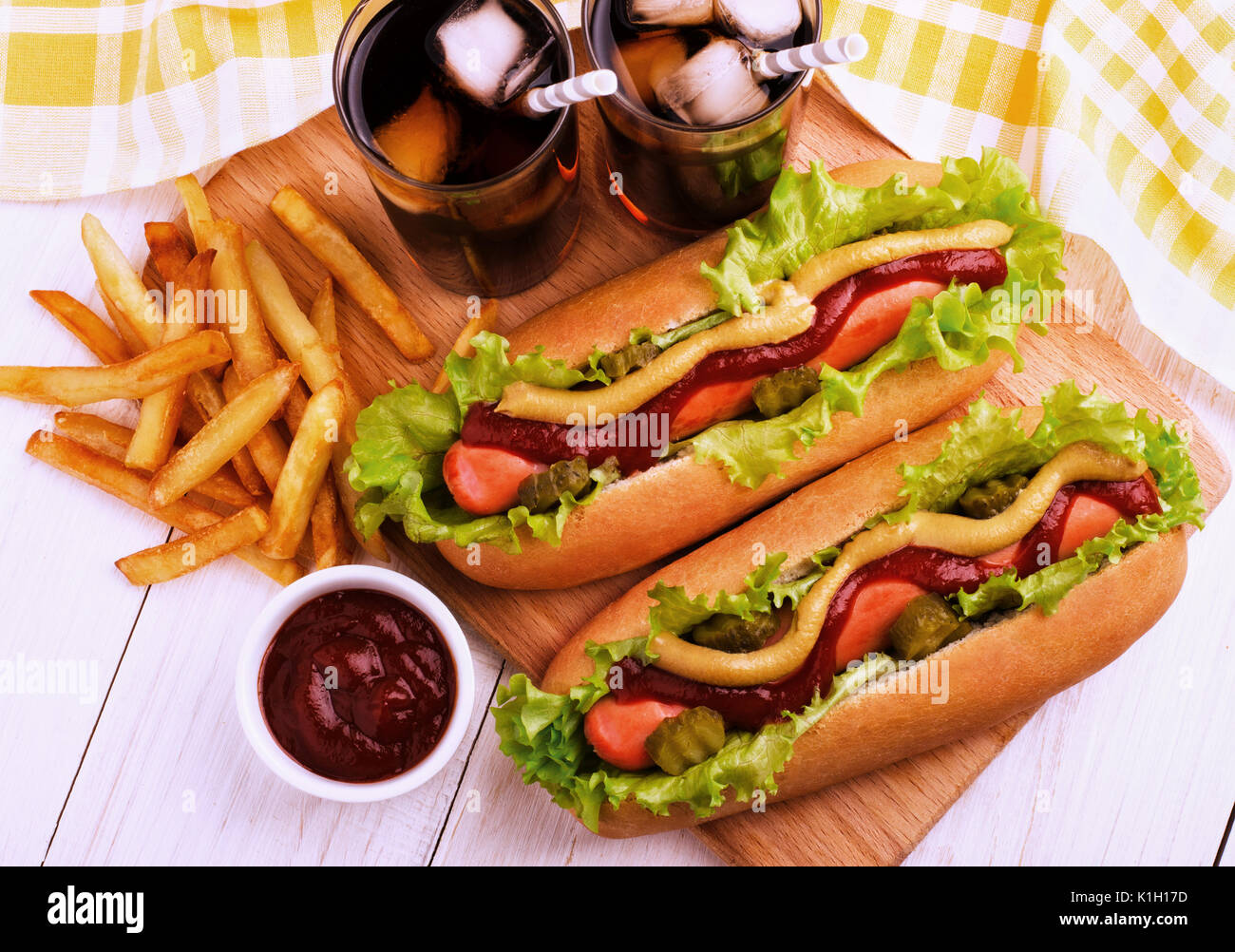 Hot dogs, potato wedges and cola on wooden board, top view. Fast food. - Stock Image
