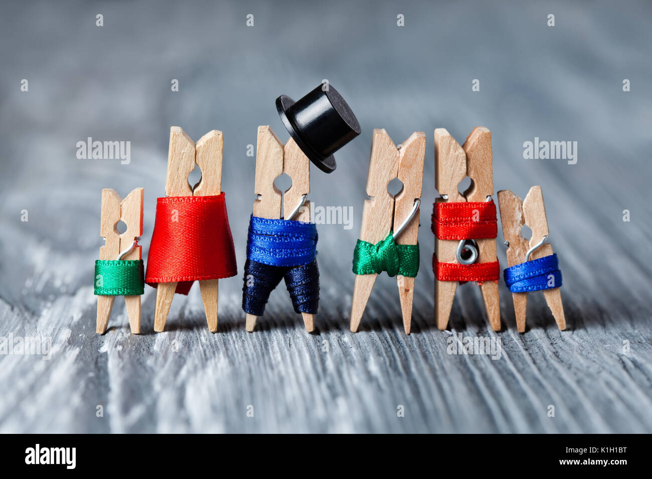 Family portrait. Concept. Playground family. Abstract: The family of linen clothespins. Man, woman with child. Man, woman, child in swimwear. (Soft focus). - Stock Image