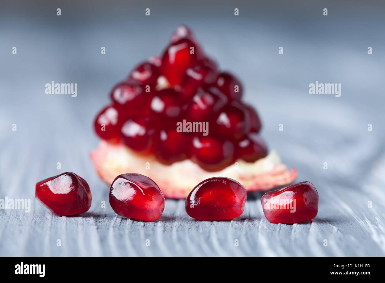 Pomegranate seeds. Part of pomegranate fruit. old gray wooden background. Macro view. (Soft focus). - Stock Image