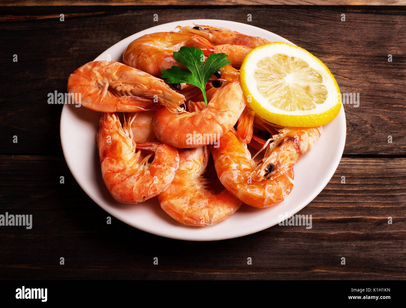 Prepared shrimp with lemon and parsley on a white plate on wooden background - Stock Image