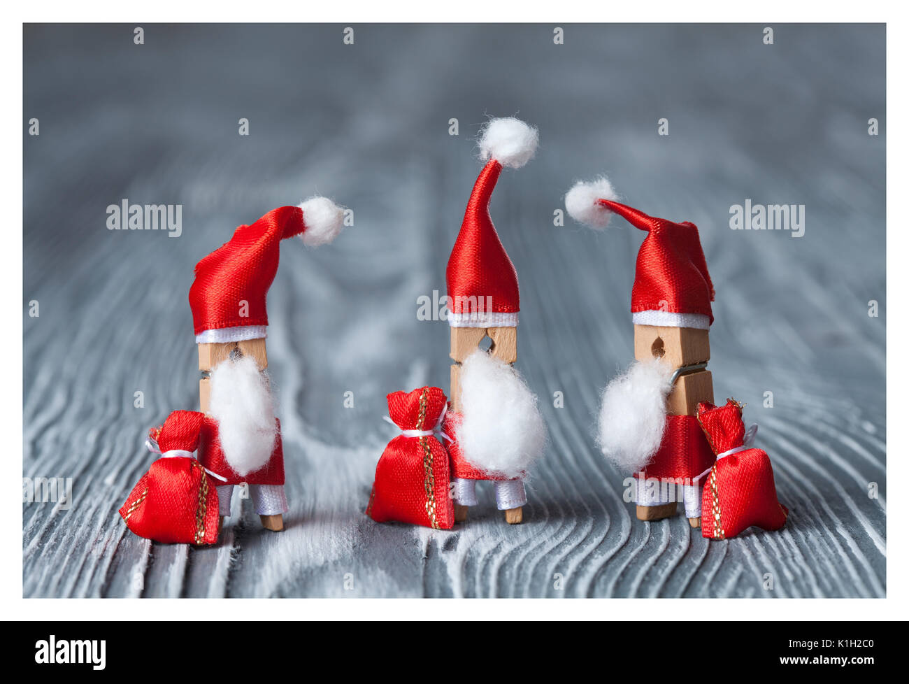 Christmas concept - clothespin. Three of Santa Claus. Retro Santa Claus  with a few bags of gifts. Father frost. Papa Noel. (soft focus, vintage  wood ...