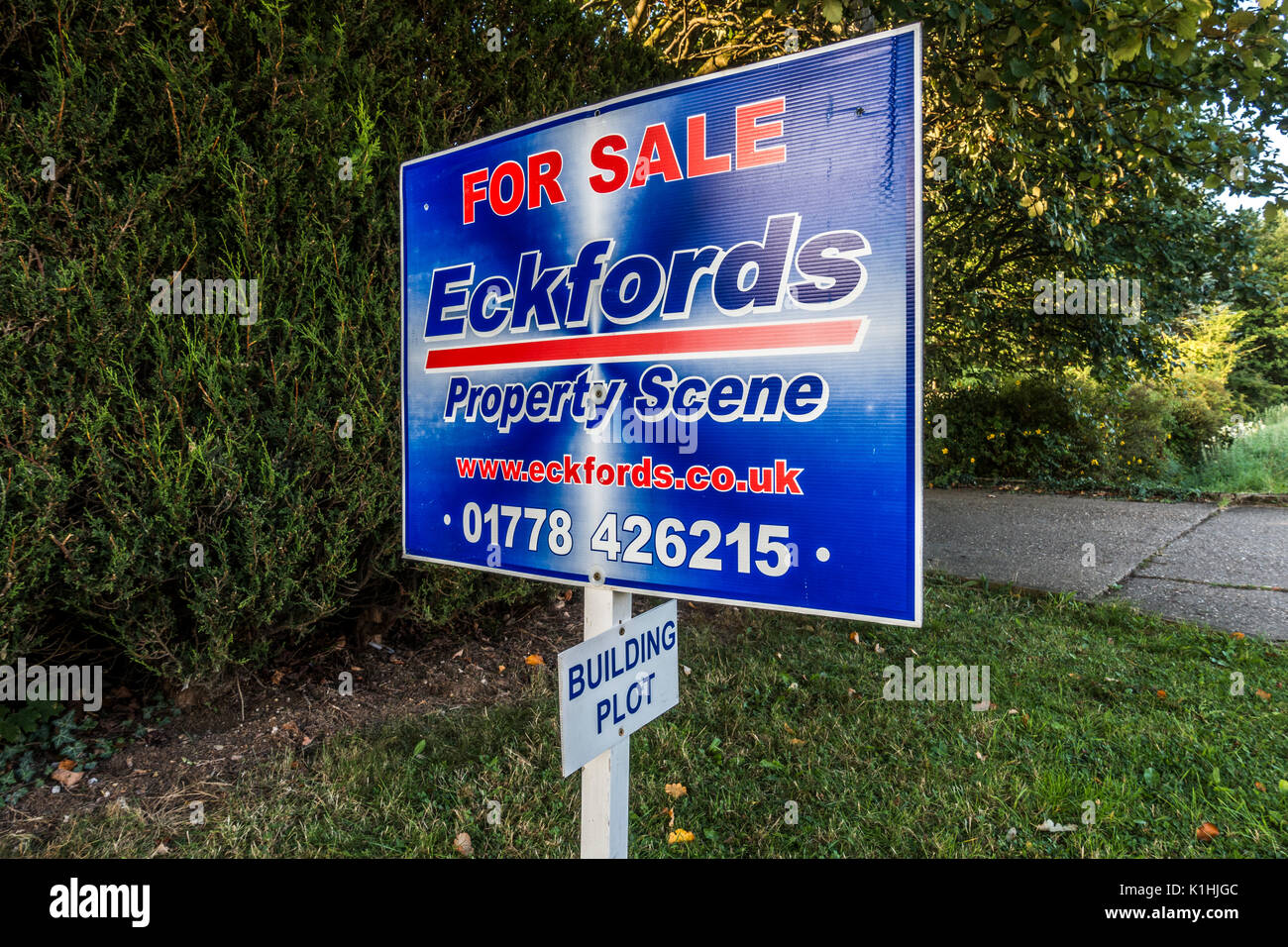 A property for sale board, with a much smaller sign to show that the agent concerned is marketing a building plot. Lincolnshire, England, UK. - Stock Image