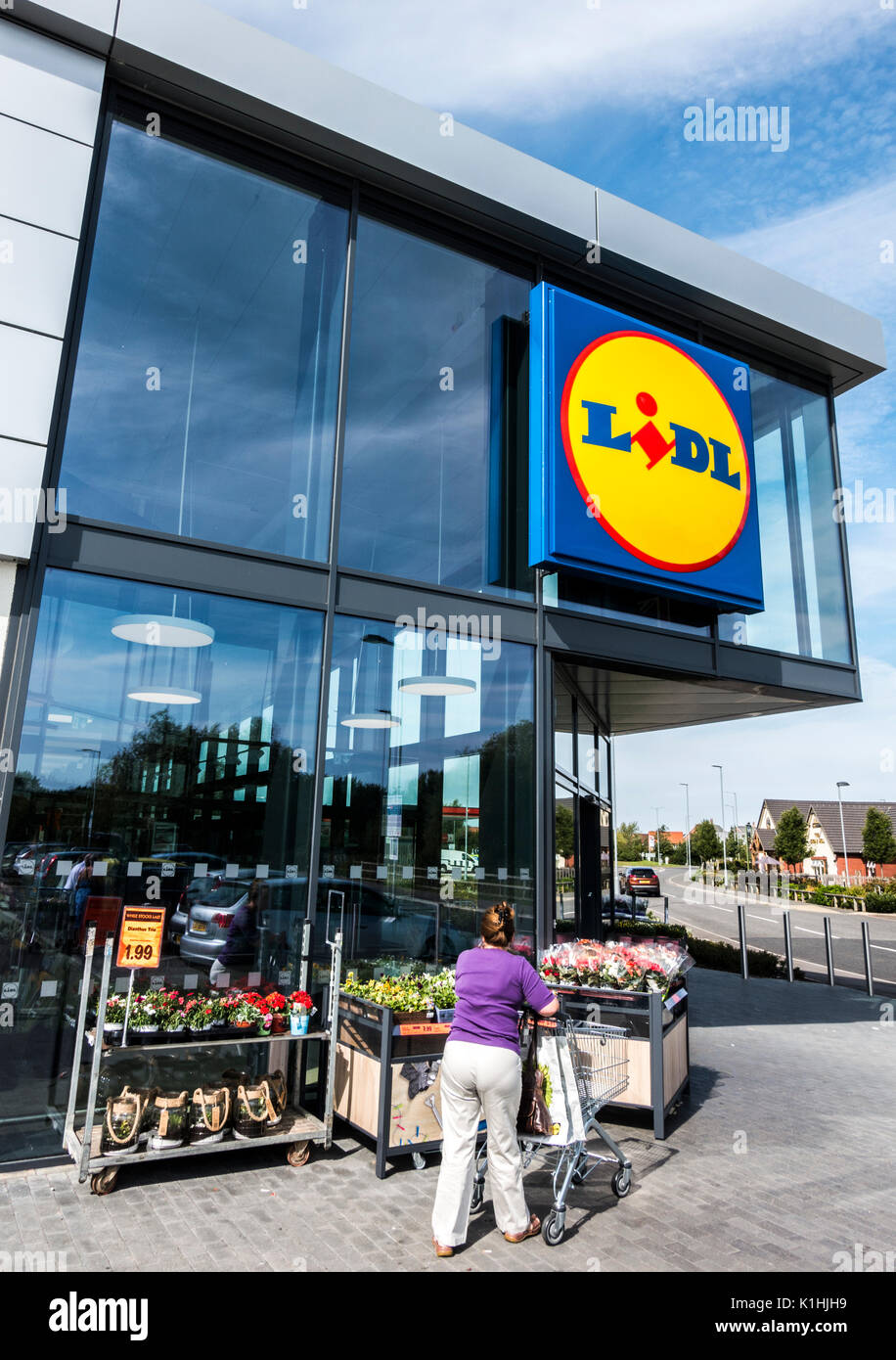 Woman pushing a shopping trolley towards the modern glass window entrance of the new and stylish Lidl supermarket, Bourne, Lincolnshire, England, UK. - Stock Image