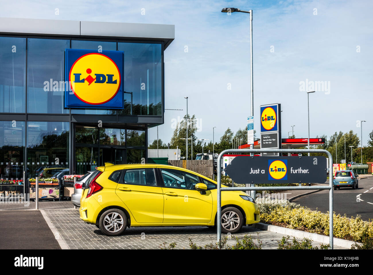 Car park and modern glass window entrance of the new and stylish Lidl supermarket in the town of Bourne, Lincolnshire, England, UK. - Stock Image
