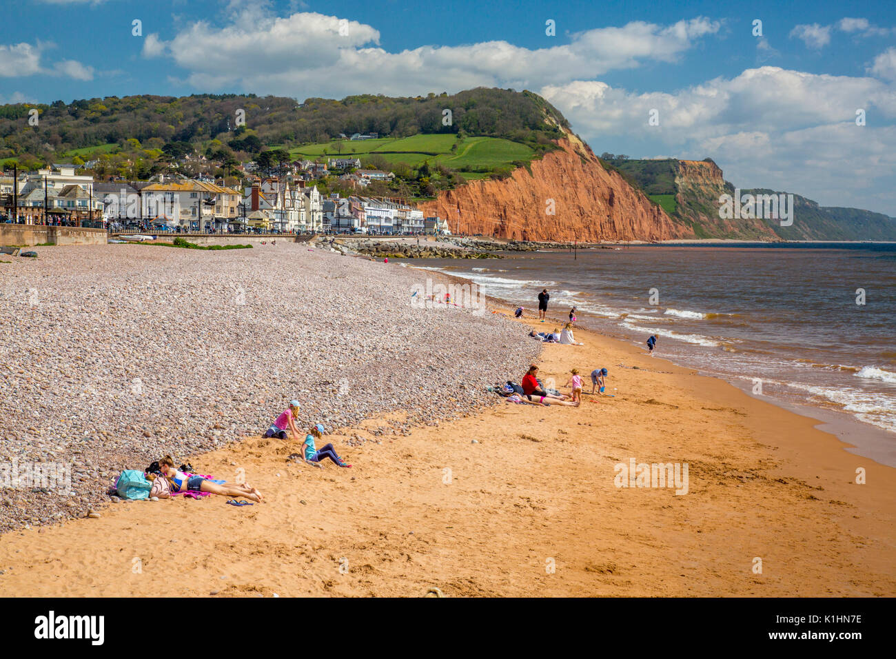 Families playing on the sandy beach at Sidmouth, a popular seaside resort on the Jurassic Coast flanked red sandstone cliffs, Devon, England, UK - Stock Image
