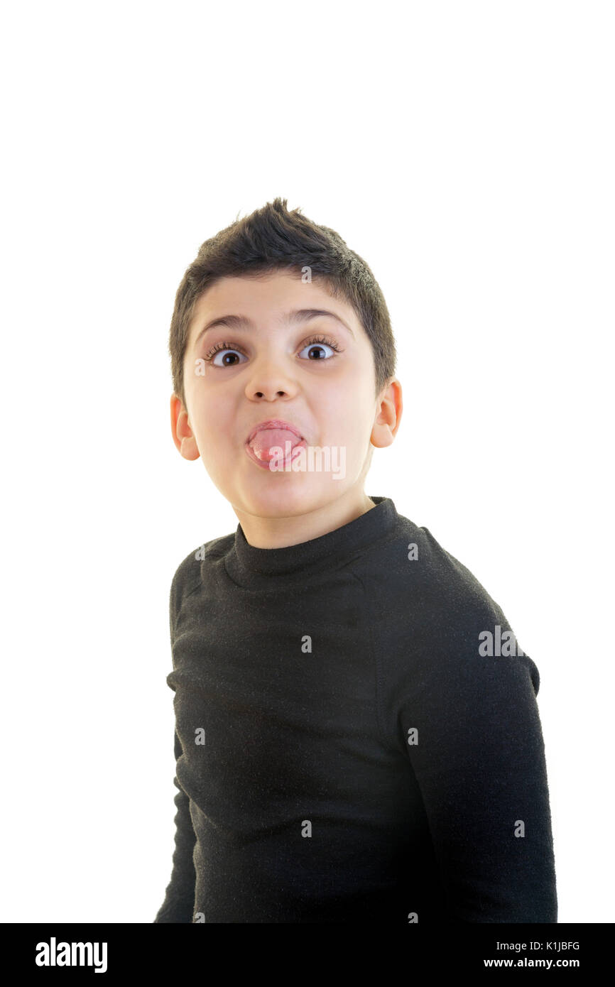 Funny little boy is sticking his toungue out and making a funny face on isolated white background. - Stock Image