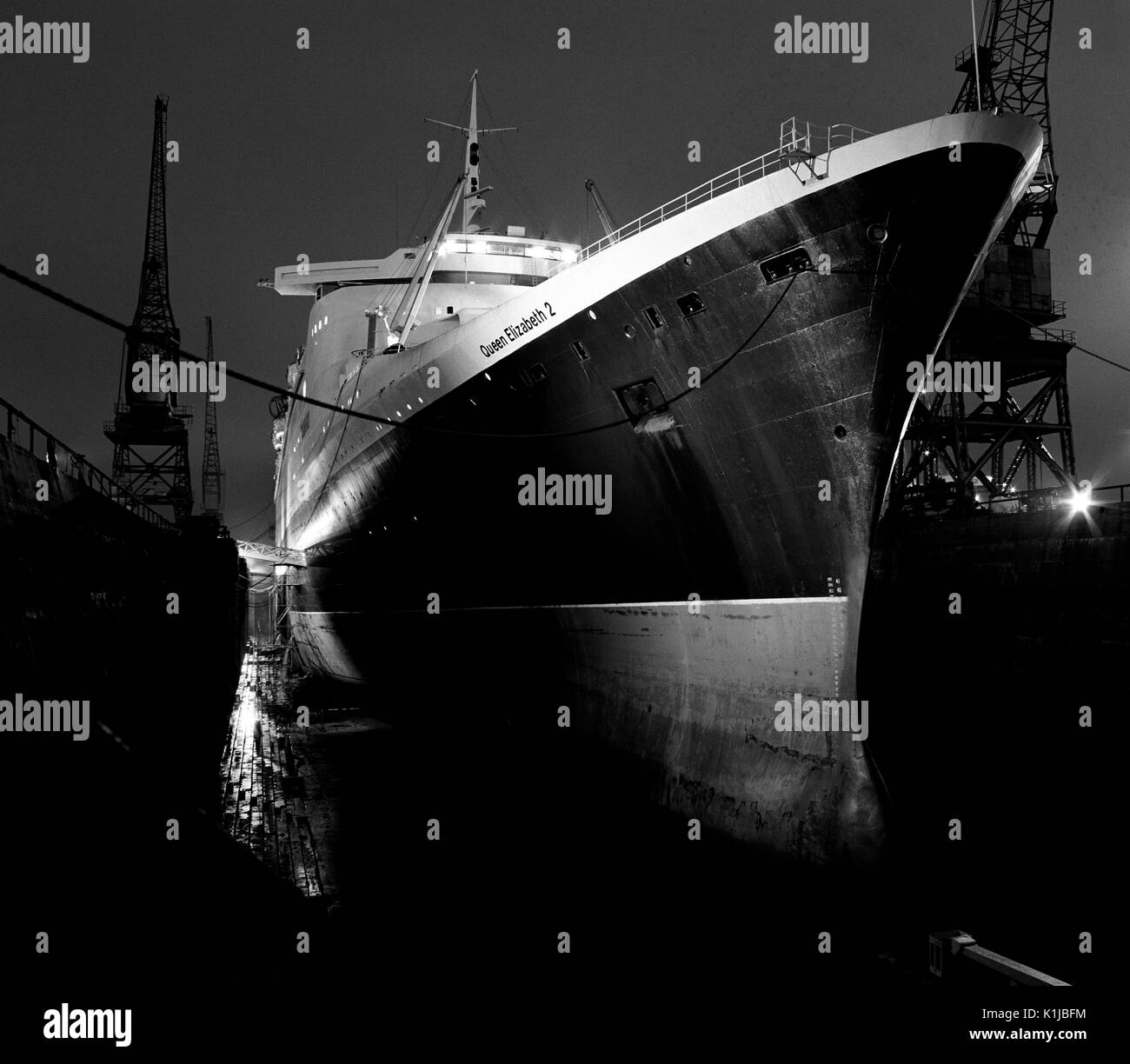 Night photograph of QE2 in the King George V dry dock at Southampton Docks, Southampton, Hampshire, England, where she is having helicopter landing pads fitted for service in the Falklands War - May 1982 - Stock Image
