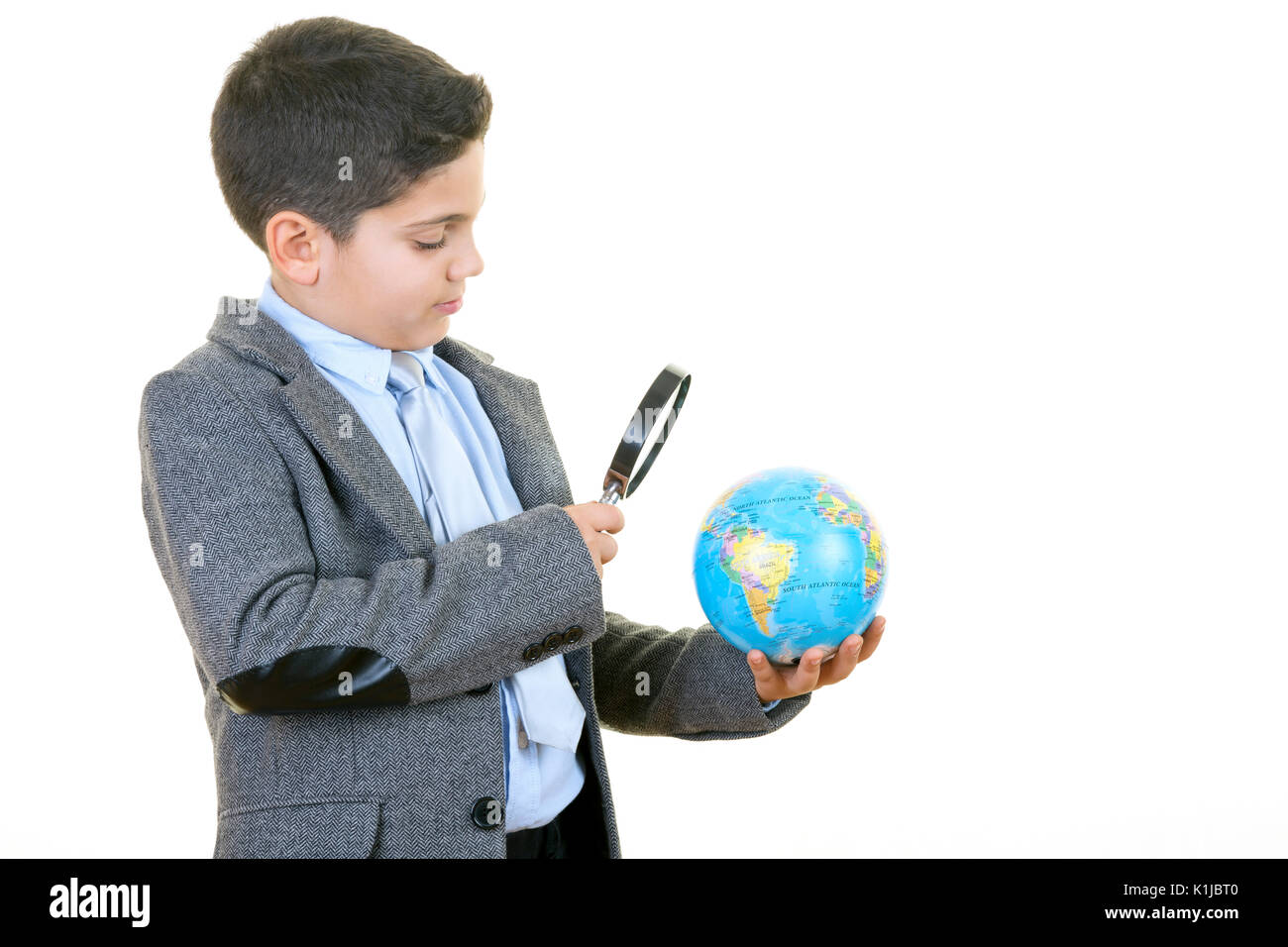 Little businessman is searching for new business opportunities with the help of his toy globe against white background. - Stock Image