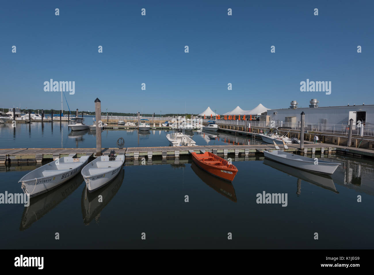 Belmar, NJ USA -- August 26, 2017 Orange and White motorboats are docked at the Belmar Marina and reflected in the water. Editorial Use Only. - Stock Image