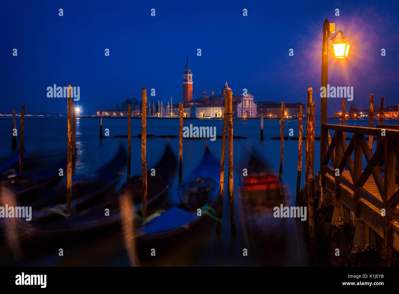 Gondolas at twilight with the island of San Giorgio Maggiore in the background. - Stock Image