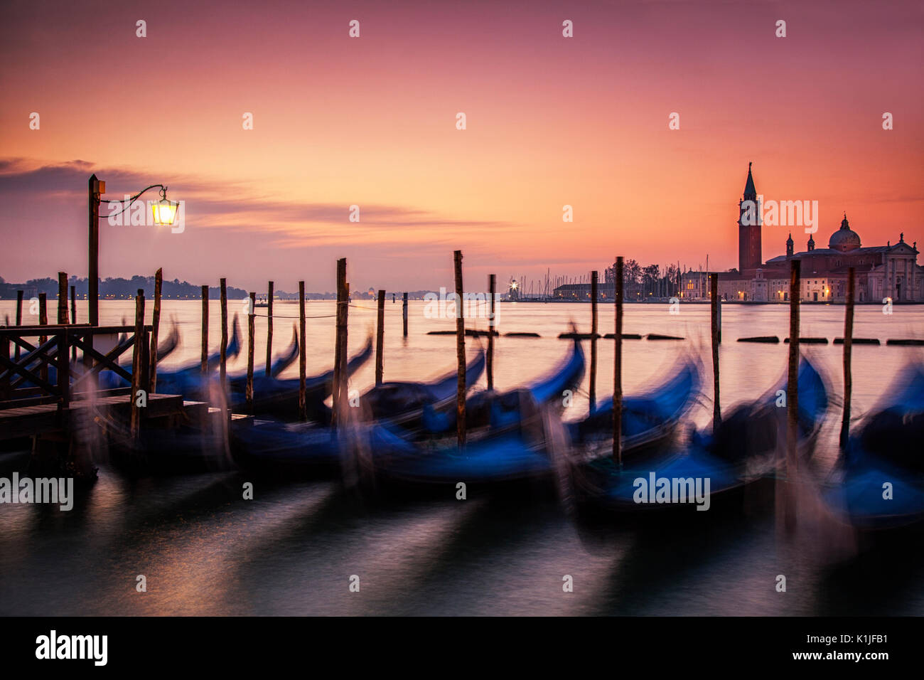 Sinrise over the gondolas of Venice, Italy and the island off San Giorgio Maggiore. Stock Photo